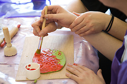 Close up of the hands of a Care Assistant helping an adult with learning disabilities to paint a piece of modeling clay,