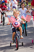 A young boy rides her bicycle decorated in red, white and blue during the I'On neighborhood Independence Day parade July 4, 2015 in Mt Pleasant, South Carolina.
