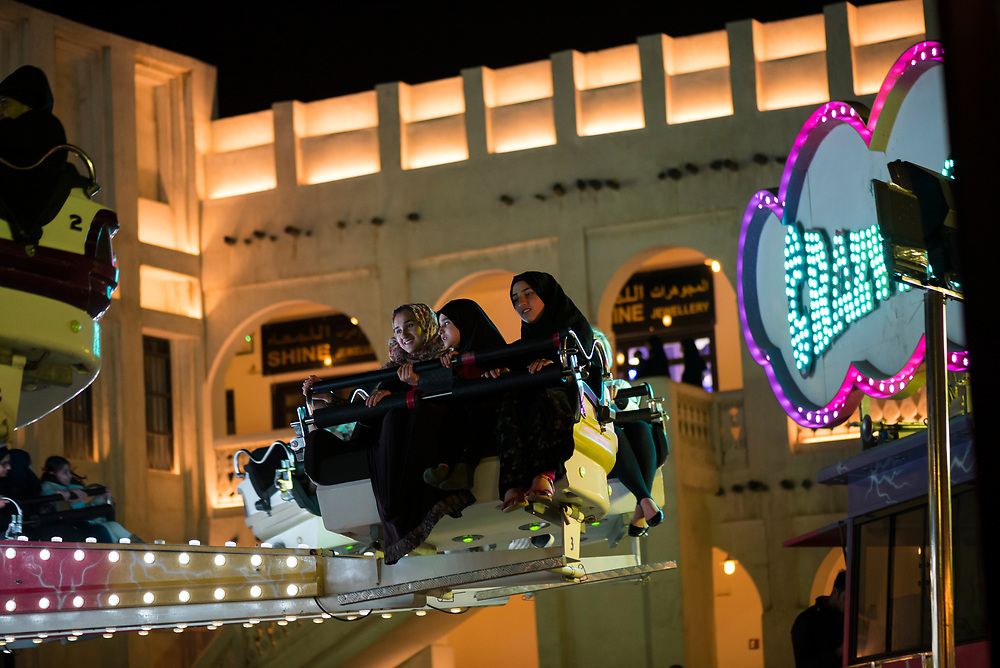 Arab girls enjoy an amusement park ride at Souk Waqif in Doha, Qatar