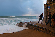 Tourists dodging Atlantic waves lashing the resort town of Biarritz, in the Basque region of France, March 2013
