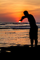 Man pushing down the sun at a beach in Cost Rica