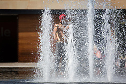 © Licensed to London News Pictures. 27/06/2015. Bradford .UK. A man cool's off in the morning heat at the water fountains in Centenary square in Bradford. Britain is set to sizzle in temperatures of up to 34C (93F) today, with forecasters predicting the hottest day for several years. A tropical air mass moving from North Africa, Spain and Portugal means that we could be hotter than Rio de Janeiro.Photo credit : Andrew McCaren/LNP