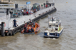 © Licensed to London News Pictures. 20/08/2013.  RNLI rescue a man from the water in the River Thames near St Katharines Pier next to Tower Bridge. Photo credit : Vickie Flores/LNP