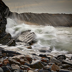 A rough sea breaking over rocks high on the beach at Hartland Quay in Devon
