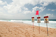 Warning signs on the North Shore of Oahu warn beach goers of the dangers of the winter surf.