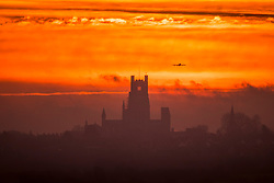 © Licensed to London News Pictures. 23/02/2021. Ely UK. An aircraft from Cambridge Airport passes Ely Cathedral in Cambridgeshire as the sky turns bright orange at dawn this morning. Photo credit: Andrew McCaren/LNP