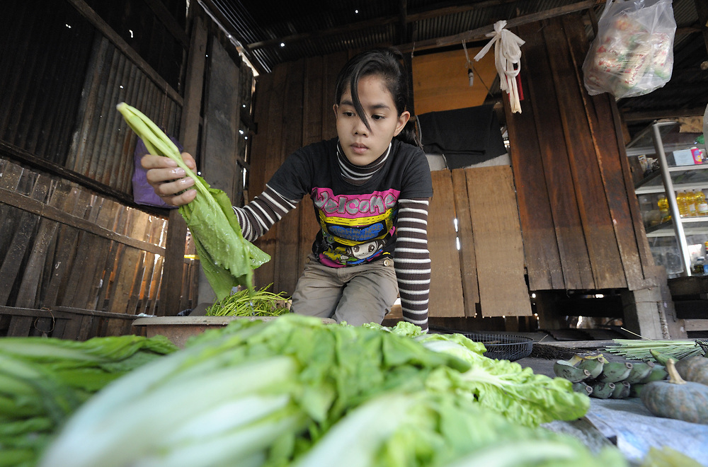 A woman sorts produce in her home store in the Chamroen neighborhood of Phnom Penh, Cambodia.