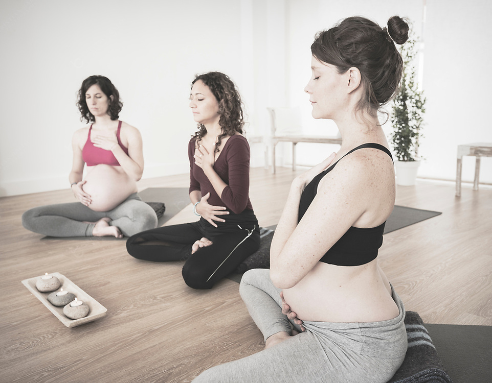 Group of pregnant woman doing breathing exercising in yoga class