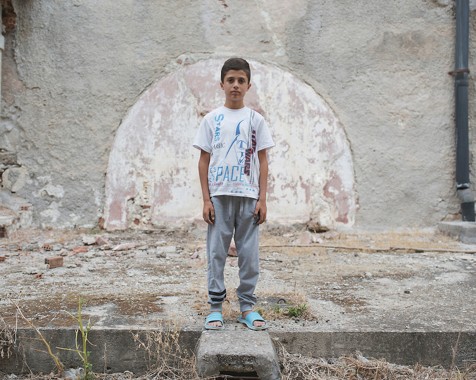 Diar, a 13 year old Syrian Kurd, stands in the ruins of the abandoned Lepida psychiatric hospital. <br /> <br /> Originally constructed, in 1930 by fascist Italy, as barracks for Italian soldiers serving in the aeronautical base of Portolago, it was then, for a short period after WWII, a re-education camp for the children of Greek Communists. In 1958, it was converted into the biggest psychiatric hospital in the country. The conditions for the patients were horrific and it was shut down in the late 1980s and the patients moved into smaller buildings in the grounds and elsewhere on the island.