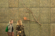 Two women look at an installation of a tree branch and leaves in the booth of the Mariam Goodman Gallery. The woman in the camouflage jacket seems to blend in to the installation.