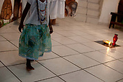Young girl walks across the altar. Ceremony at Terreiro (yard) peace and love / Terreiro Paz y Amor, Salvador, Bahia, Brazil. Often the lines between Candomble, Catholicism and Umbanda are blurred. Salvador de Bahia is seen as the home of Candomble.