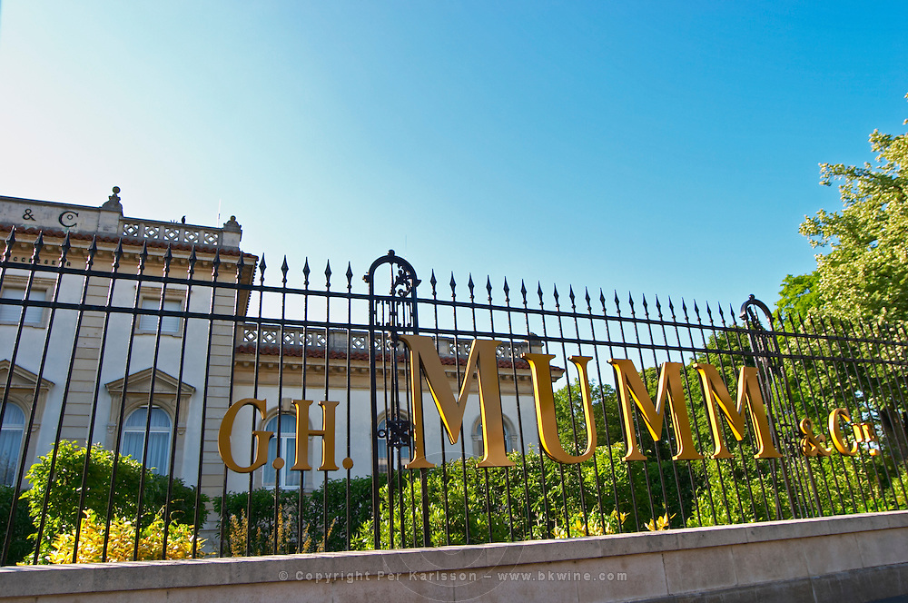 A wrought iron fence and golden letters in the setting sun at Champagne G.H. Mumm with the champagne house in the background, Reims, Champagne, Marne, Ardennes, France