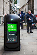 A modern refuse bin outside Bank Underground Station in London, United Kingdom.  The bin has separate sections for general waste and recycling.  The bin also has a digital screen which displays a message about the amount of recycling that Renew has achieved in London.