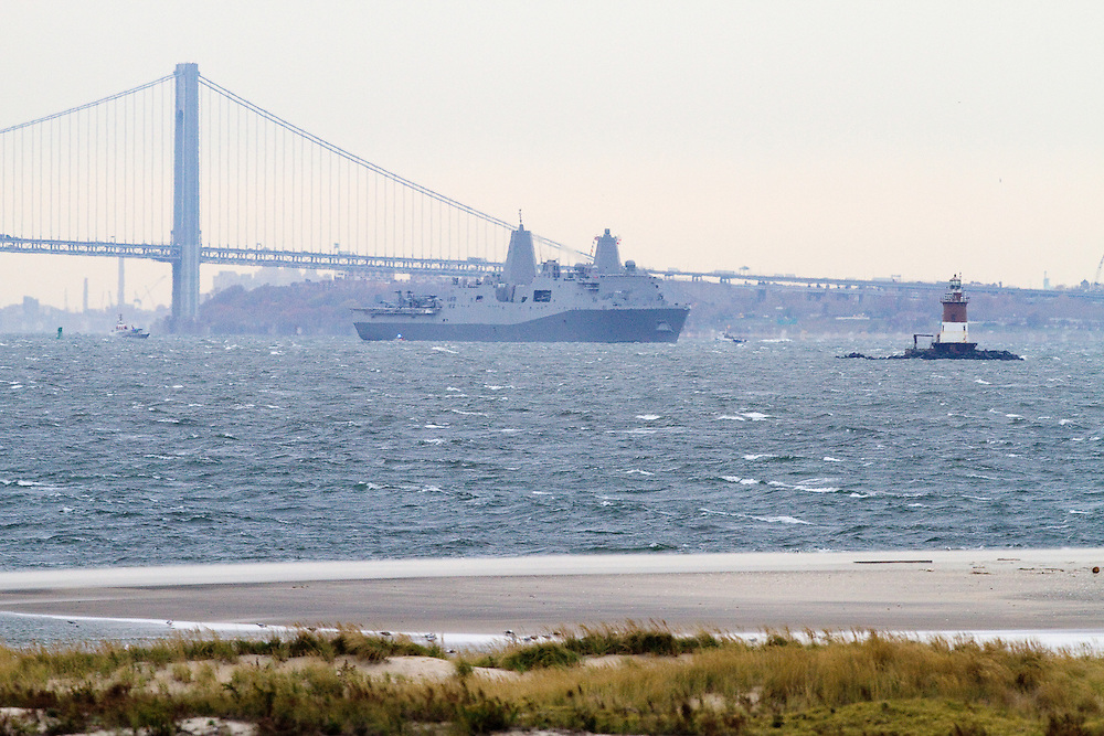 The USS New York built with steal salvaged from the World Trade Center Towers and after having been commissioned in a ceremony on November 8th in New York City sailes out from under the Varranzano-Narrows Bridge as it leaves New York City and New York Harbor.    To the right is the Romer Shoal Lighthouse.