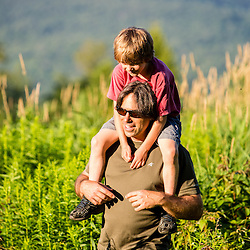 A man carries his son on his shoulders in a field in Duxbury, Vermont.