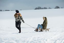 Teenage girl pulling sled in snowy landscape in winter, Bavaria, Germany