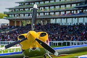 Preparations in the 'pit lane' as mechanics mingle with 'VIP' guests. - Red Bull Air Race World Championships at Ascot Race Course. A combination of high speed, low altitude and extreme manoeuvrability make it only accessible to the 'world's most exceptional pilots'. 12 pilots compete in the Master Class category in eight races across the globe for the title of 2014 Red Bull Air Race World Champion. The objective is to navigate an aerial racetrack featuring air-filled pylons in the fastest possible time, incurring as few penalties as possible. All 12 pilots race with a standardised propulsion package – a high-performance, race-tuned standardised engine (Lycoming Thunderbolt) and standardised propellers (Hartzell 3-bladed). They do have a chooice of 3 single engine/seater aircraft - the Zivko Aeronautic Edge 540, the MXS-R and the Hungarian University of Aviation's Corvus Racer 540 - all cappable of around 230kts and of surviving high G forces, 10+. A new feature of the 2014 Red Bull Air Race World Championship is the debut of the new Challenger Cup, giving a new generation of talented pilots from around the world a chance to race. Entertainement is provided by the Red Arrows and the Breitling Wingwalkers, amongst others.  Ascot Racecourse, High St, Ascot, Berkshire, UK.