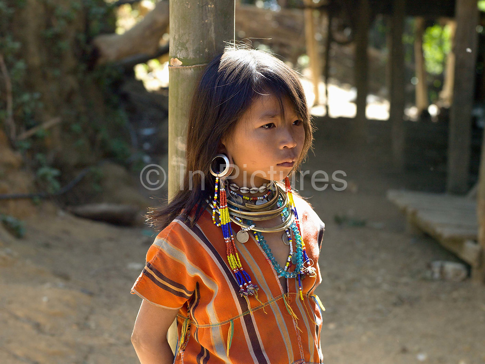 Portrait of  Kayaw ethnic minority girl on 19th January 2016 in Kayah State, Myanmar. Wearing traditional costumes made from handwoven cotton, Kayaw women wear many necklaces made from shells, beads and brass coils and fashioned from silver. Distended earlobes are plugged with rings of silver and the ankles and knees encased with brass coils