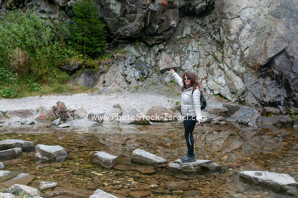 Woman skips over stepping stones placed in a pond. Photographed on the 'Wild Water Way' Stubai, Tyrol, Austria