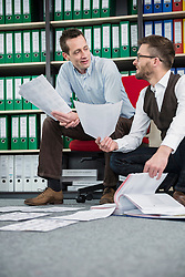 Two men office organizing document filing