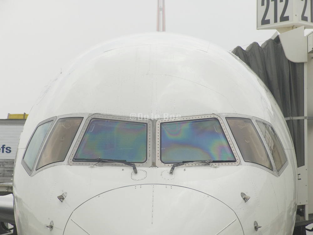 Front view of passenger jet airplane while docked.