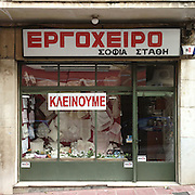 """A embroideries shop in  in Frontzou Str, Ioannina. The sign reads """"We are closing down"""""""