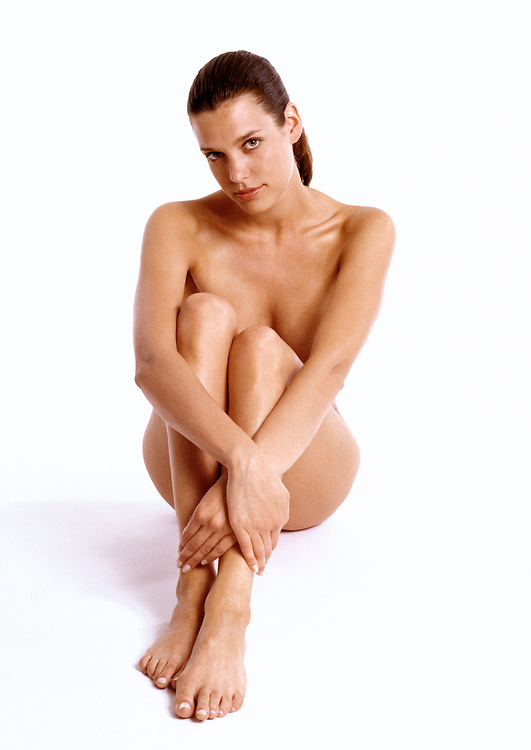 Nude woman sitting on a white background with legs crossed