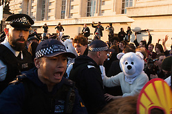 London, March 7th 2015. Following the Climate march through London, masked anarchists and environmental activists clash with police following a breakaway protest at Shell House. PICTURED: A man dressed in a polar bear suitlooks on as a TSG officer shouts at activists blocking the path of a police van containing a colleague of the protesters arrested earlier.