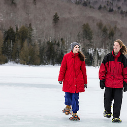 A teenage boy and girl snowshoeing on Henderson Lake on the Tahawus Tract, Newcomb, New York. Adirondack Mountains. One source of the Hudson River.