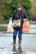 © Licensed to London News Pictures. 09/02/2014. Wraysbury, UK. A woman carries shopping along a flooded road.  Flooding in Wraysbury in Berkshire today 9th February 2014 after the River Thames burst its banks. Photo credit : Stephen Simpson/LNP
