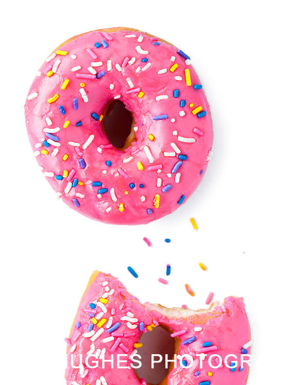 Glazed donut with pink frosting and sprinkles