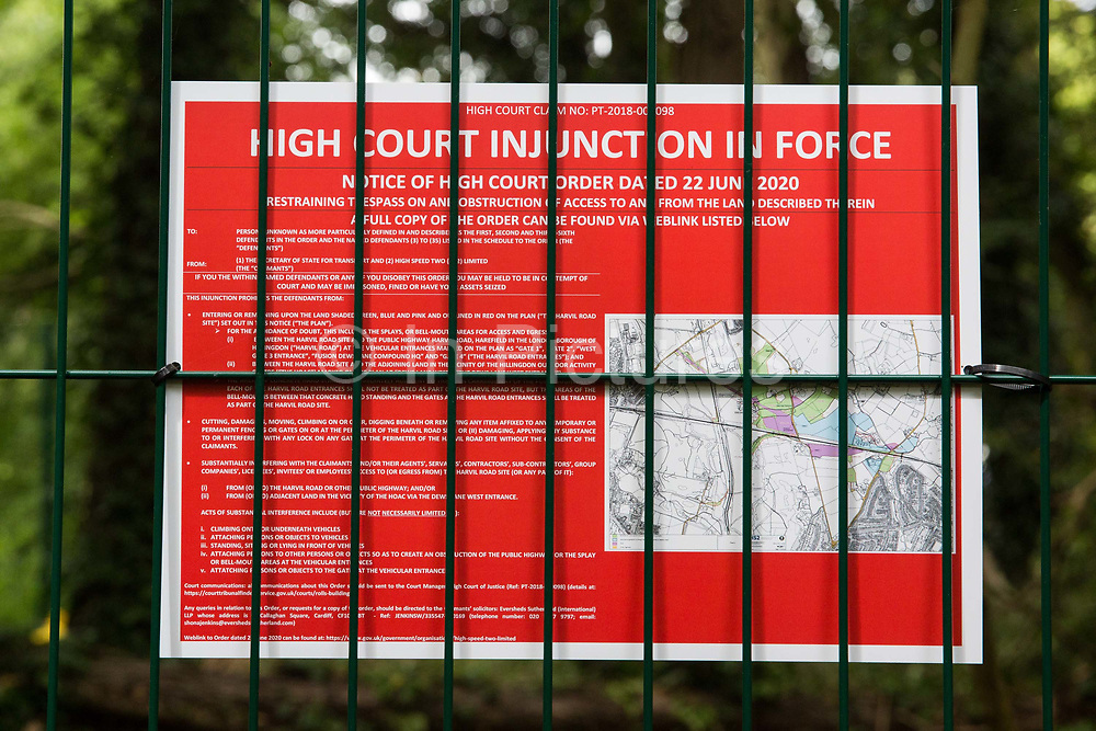 A High Court injunction notice is seen inside fencing around a compound in woodland recently established by HS2 workers to facilitate tree felling on 13th July 2020 in Denham, United Kingdom. The HS2 project is currently projected to cost around £106bn and will remain a net contributor to CO2 emissions during its projected 120-year lifetime.