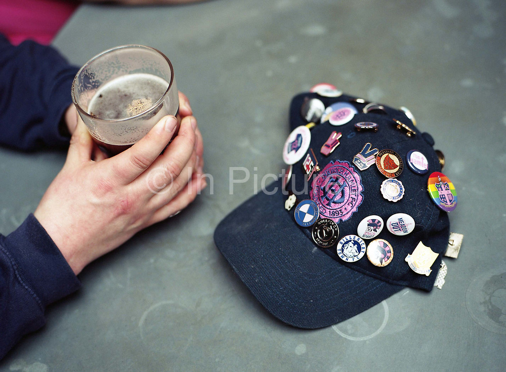 Two hands holding a pint next to a Dulwich Hamlet baseball cap covered with football pin badges ahead of the Dulwich Hamlet game against Truro City on the 16th March 2019 at Champion Hill in South London in the United Kingdom.