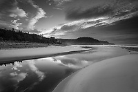 Clouds reflect in on the sureface of a tidal river along the shores of Cape Breton Island, Nova Scotia Canada.  Black and white
