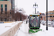 08 FEBRUARY 2021 - DES MOINES, IOWA: A city worker plows snow on the Court Ave Bridge over the Des Moines River in downtown Des Moines. Central Iowa, including Des Moines, is enduring its coldest winter in 25 years. Daily high temperatures this week are not expected to go above 10F (-12C) and nightly lows are expected to be about -5F (-20C). In addition to the cold weather, this is the second snowiest winter in Des Moines history. So far this winter there has been more than 44 inches (111 centimeters) of snow. Des Moines normally gets about 35 inches (90 centimeters) of snow all winter.        PHOTO BY JACK KURTZ