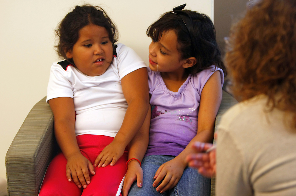 Fernanda Garcia-Villanueva, 8, (L) squeezes into a chair with her cousin visiting from Mexico during a counseling session with Marilyn Day (R) Shapedown Program director at The Children's Hospital in Aurora, Colorado July 8, 2010.  Shapedown is part of the child and teen weight management programs at the hospital.  REUTERS/Rick Wilking (UNITED STATES)