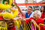 "10 FEBRUARY 2013 - BANGKOK, THAILAND: People pet and place money into the ""mouth"" of a Lion during a Lion Dance on Chinese New Year along Yaowarat Road in the Chinatown section of Bangkok. Bangkok has a large Chinese emigrant population, most of whom settled in Thailand in the 18th and 19th centuries. Chinese, or Lunar, New Year is celebrated with fireworks and parades in Chinese communities throughout Thailand. The coming year will be the ""Year of the Snake"" in the Chinese zodiac.    PHOTO BY JACK KURTZ"