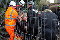 Harefield, UK. 16 January, 2020. Enforcement agents working on behalf of HS2 prevent Stop HS2 activist Mark Keir from reentering the Harvil Road wildlife protection camp in the Colne Valley after it was agreed that he could bring out dogs to a woman waiting outside belonging to a fellow activist evicted earlier in the morning from the camp after two days spent in a tree in woodland.