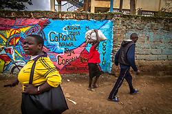 May 9, 2020: Residents find their way past a wall with witten Corona Virus Preventive measure  message. (Credit Image: © Donwilson Odhiambo/ZUMA Wire)