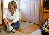 Barb Kotzian sits on the floor to put on her shoes at her home in Thornton, Colorado March 31, 2010.  About four-feet-tall,  Barb and her husband are both achondroplasia dwarfs, a rare genetic disorder of bone growth.  Preferring to be called little persons they both are active in the Little People of America, the only dwarfism support organization that includes all 200+ forms of dwarfism.  REUTERS/Rick Wilking (UNITED STATES)