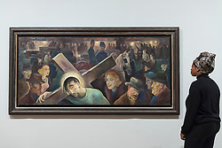 "© Licensed to London News Pictures. 04/06/2018. LONDON, UK. A gallery staff member views ""Cross Shouldering (Friedrichstraße), Kreuztragung Friedrichsrasse"", 1924, by Albert Birkle at a preview of ""Aftermath:  Art in the wake of World War One"" at Tate Britain.  The exhibition marks 100 years since the end of the First World War, exploring the impact of the conflict on British, German, and French art in over 150 works from 1916 to 1932.  The show runs 5 June to 23 September 2018.  Photo credit: Stephen Chung/LNP"