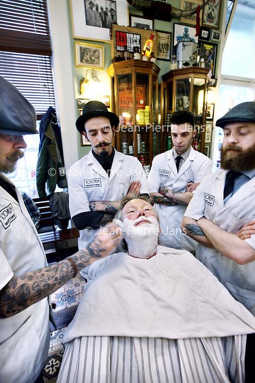 """Nederland, Rotterdam , 6 november 2013.<br /> Haarsnijder en Barbier Schorem aan de Nieuwe Binnenweg in R'dam.<br /> Eindelijk is het zover, Leen en Bertus openen de deuren van de enige vrouwvrije zone in Rotterdam. Dames, we zijn gek op jullie, maar wij zijn van mening dat elke man recht heeft op een plek waar hij even man kan zijn, en daarom hebben wij besloten het oude ambacht van barbier nieuw leven in te blazen. Geen gezeik, knippen en scheren! Stap terug in de tijd, stap binnen bij Schorem Haarsnijder en Barbier!<br /> Op de foto"""" Geheel links 1 vd initiatiefnemers Bertus en links in de stoel, hoofdredacteur Marketing Tribune Sjaak Hoogkamer.<br /> Foto:Jean-Pierre Jans"""
