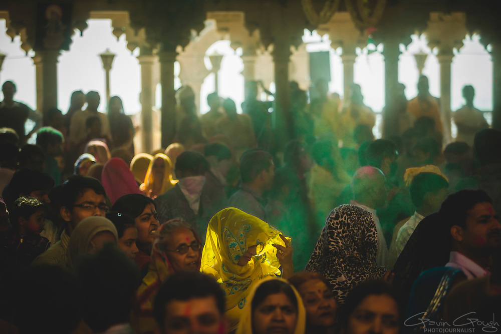 A crowd gathered inside the temple during Holi festival celebrations where sunlight illuminates a woman's sari, Radha Rani Temple, Barsana, India