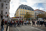 Pedestrians cross a road on the 29th of October 2019 as a tram passes through a busy Luis de Camoes square, Lisbon, Portugal.