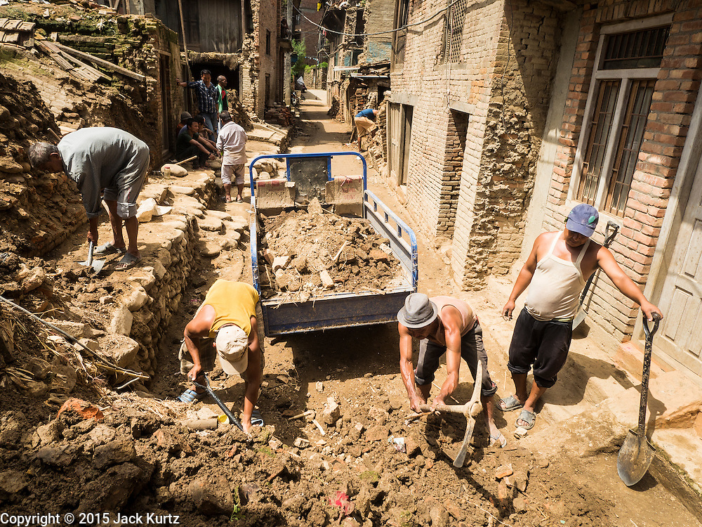 04 AUGUST 2015 - BUNGAMATI, NEPAL: Men dig out a residential street in Bungamati, a village about an hour from Kathmandu. Three months after the earthquake debris from the earthquake still clogs many of the streets in the community. The Nepal Earthquake on April 25, 2015, (also known as the Gorkha earthquake) killed more than 9,000 people and injured more than 23,000. It had a magnitude of 7.8. The epicenter was east of the district of Lamjung, and its hypocenter was at a depth of approximately 15km (9.3mi). It was the worst natural disaster to strike Nepal since the 1934 Nepal–Bihar earthquake. The earthquake triggered an avalanche on Mount Everest, killing at least 19. The earthquake also set off an avalanche in the Langtang valley, where 250 people were reported missing. Hundreds of thousands of people were made homeless with entire villages flattened across many districts of the country. Centuries-old buildings were destroyed at UNESCO World Heritage sites in the Kathmandu Valley, including some at the Kathmandu Durbar Square, the Patan Durbar Squar, the Bhaktapur Durbar Square, the Changu Narayan Temple and the Swayambhunath Stupa. Geophysicists and other experts had warned for decades that Nepal was vulnerable to a deadly earthquake, particularly because of its geology, urbanization, and architecture.    PHOTO BY JACK KURTZ