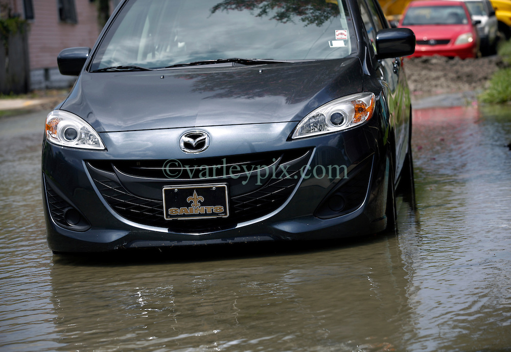 23 July 2013. New Orleans, Louisiana.<br /> A local resident's car stuck in flood water. Following a major break in an old 30-inch water main, officials and workers from New orleans Sewerage and Water board struggle to contain the millions of gallons of water flooding homes and streets in The Carrolton neighbourhood. Huge investment in public infrastructure is required to repair and upgrade the ageing water delivery system in the city. Following the break, low water pressure and a public boil advisory affected tens of thousands of Uptown residents.<br /> Photo; Charlie Varley