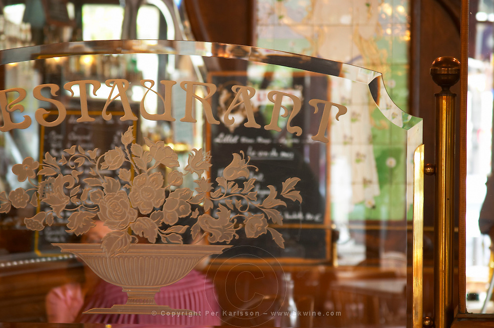 Detail of a glass partition partitioning facetted and engraved etching text Restaurant and a bouquet of flowers. In the background mirrors and the menu The Bistrot du Peintre is an old fashioned Paris café cafe bar restaurant of art nouveau design with polished brass, mirrors and old signs