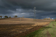 Power lines cross a prepared field in Warwickshire landscape on 10th November 2020 near Henley-in-Arden, United Kingdom.