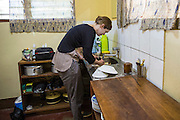 VSO volunteers Dr Siobhan Neville washing up in her home kitchen on the campus of St Walburg's Hospital, Nyangao. Lindi Region, Tanzania.