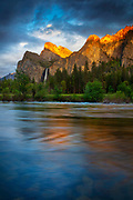 The golden light of sunset reflects off several Yosemite peaks, including the Cathedral Rocks and Leaning Tower, onto the Merced River at Valley View in Yosemite National Park, California. Bridalveil Fall, a 620-foot (189-meter) waterfall, is visible across Bridalveil Meadow.